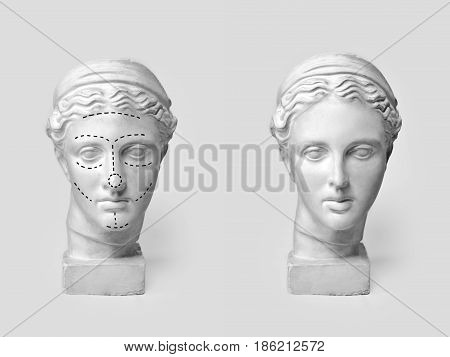 Two marble heads of young women, ancient Greek goddess bust marked with lines for plastic surgery and sculpture after operation on light background. Old and new beauty standarts concept