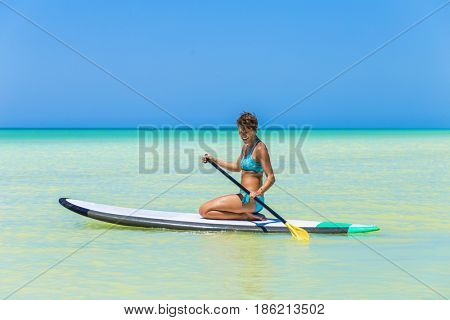 Woman practicing SUP yoga, on a paddle board in the Caribbean