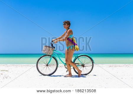Woman with a bike and a yoga mat in a Caribbean beach, in Mexico.
