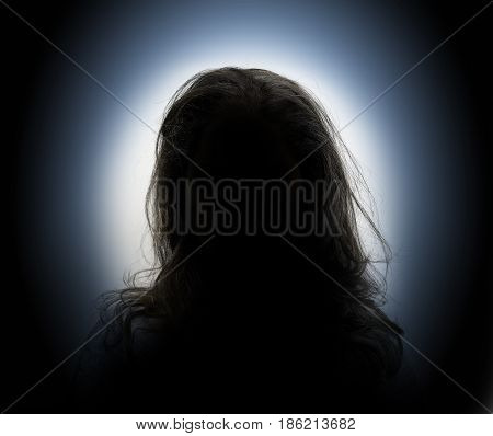 Woman head and shoulders silhouette on backlit