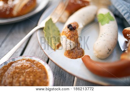 Bavarian food with white sausage and pretzel on a plate of stoneware