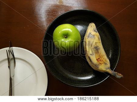 Green Apple and Banana on the black ceramic plate beside white plate with fork and knife on the wooden table - a little light reflect from lamp