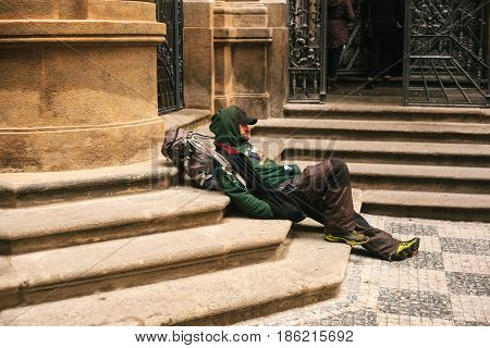 Prague, Czech Republic December 24, 2016 - Homeless hungry poor man sitting on the sidewalk in the city center. Unhappy man