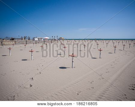 Deserted beach with the supports used to secure the parasols.