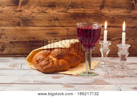 Shabbat concept with wine glass and challah bread on wooden table