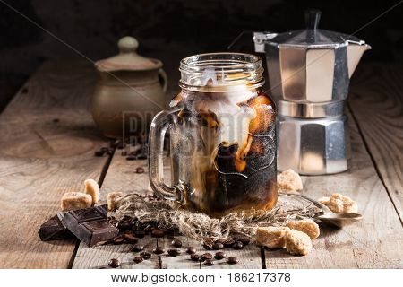 ice coffee in a jar mug with cream and coffee beans, pieces of chocolate, coffee pot on a wooden background
