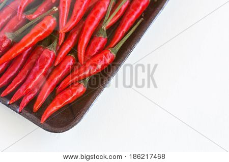 red hot chili peppers, popular spices concept - store packing of weighted red spicy peppers, peppers packing under plastic film in a dark disposable tray on white background - space for text