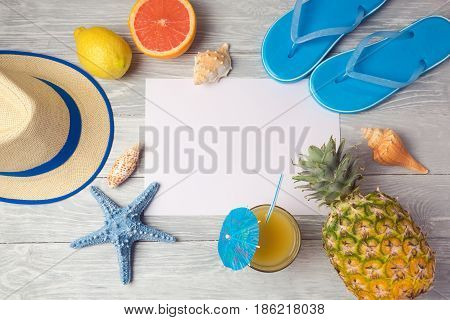 Tropical summer vacation background with blank paper pineaplle; juice and flip flops on wooden table. View from above. Flat lay