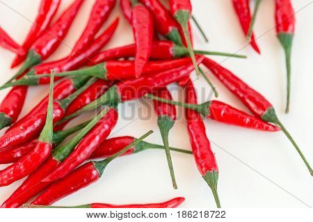 red hot chili peppers, popular spices concept - placer of beautiful red hot chili peppers, pods freely scattered on white background, top view, flat lay, isolated