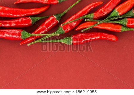 red hot chili peppers, popular spices concept - close-up on a beautiful handful of red hot pepper pods scattered on red background, top view, flat lay, free space for your text