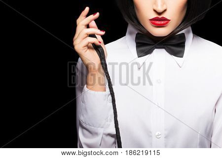 Sexy dominatrix in wig and red lips posing with whip closeup isolated on black
