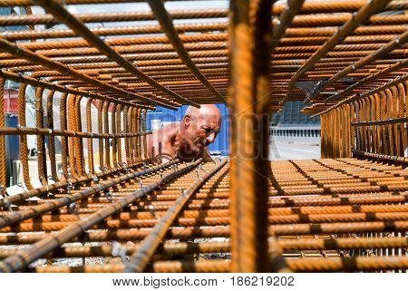 Worker Tying Rebar For Construction