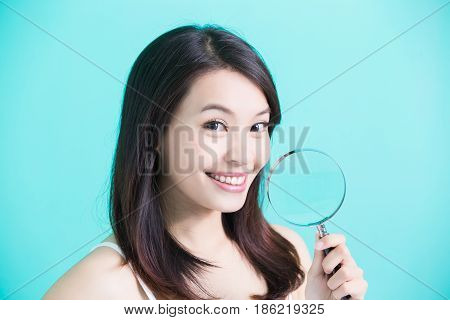 beauty skincare woman smile and take magnifying on green background