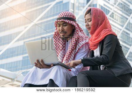 Arab Businessman and Businesswoman using computer finance concept