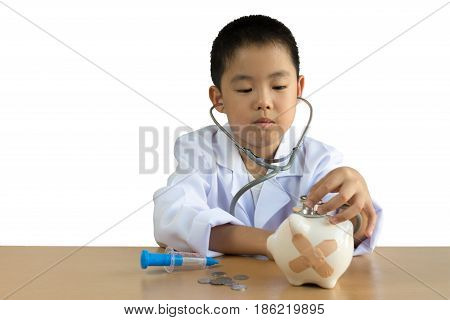 Asian boy playing as a doctor care Piggy Bank isolated background with clipping path.