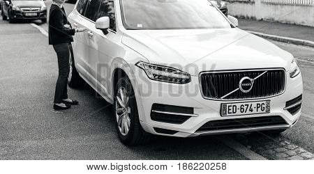 PARIS FRANCE - APR 2 2017: French woman aproaching her luxury white Volvo XC90 the luxury crossover SUV manufactured and marketed by Volvo Cars