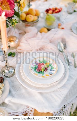 picnic, food, holiday concept - holiday decorated table with white tablecloth, stack of white plates with floral pattern, two acorns on top, burning candle in candlestick, flowers, plates with fruits