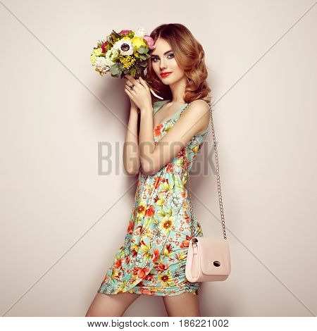 Blonde young woman in elegant floral dress. Girl posing on a beige background with handbag. Jewelry and hairstyle. Lady with spring bouquet of flowers. Fashion photo