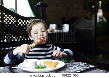 Hungry child eating kebab in a restaurant