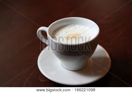 Cup of cappuccino on a wooden table