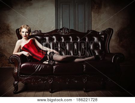 Sexy beautiful young woman dressed in a corset stockings and panties lying on sofa. Retro (vintage) style