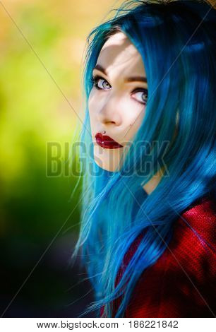 Close-up portrait of a pretty young girl with blue hair