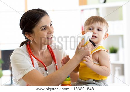 Doctor pediatrician using nasal aspiration for child. Mucus suction patient kid baby.