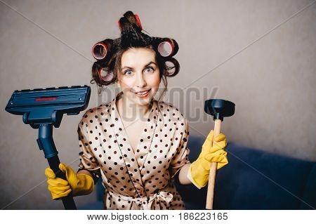 girl in a dressing gown with curls on her head curlers holds a plunger and a brush from a vacuum cleaner. The concept of cleaning the house of dust and dirt.