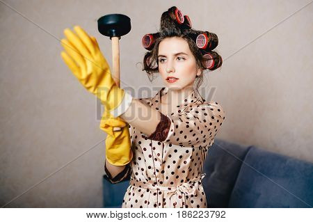 curum hair woman in clothes for the house holds a plunger and puts on a brittle rubber glove. Concept clean the blockage with their own hands.