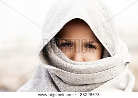 Little child boy wearing arabian nikab or hijab muslim religion style clothing