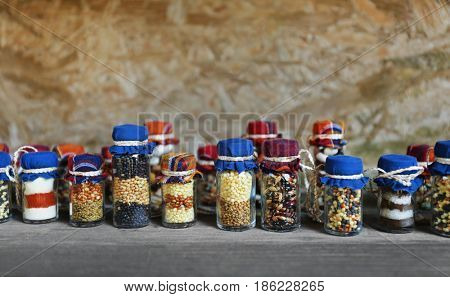 Beautiful jars with grains, cereals, legumes and seeds on wooden background