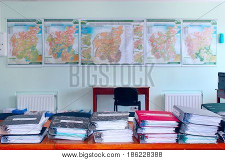 Working folders in the office with cartography on the wall. Working atmosphere in the office