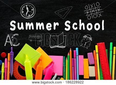 Text SUMMER SCHOOL and stationery on blackboard background