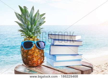 Reading during summer vacation. Books, pineapple and sunglasses on landscape background
