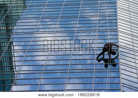 Industrial mountaineering worker wash windows of a high-rise building