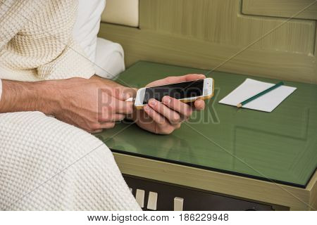 Man Connecting his Mobile Phone to a Charger While Lying on his Side on the Bed Wearing Bathrobe