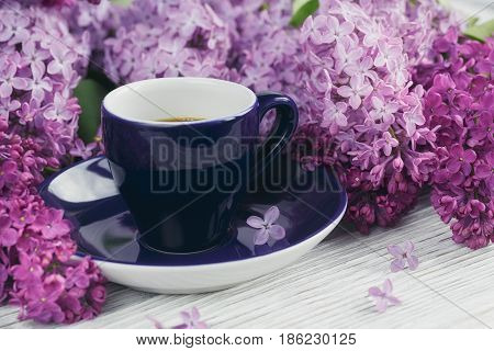 Cup of black coffee lilac flowers and sweet pastel french macaroons on white wooden table