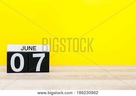 June 7th. Day 7 of month, calendar on yellow background. Summer day, empty space for text.