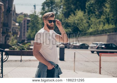 Young Hot Bearded Guy In Sunglasses And Casual Clothes Is Walking Outside. He Looks Serious, Fixing