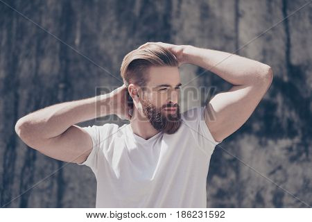 Stylish Young Red Bearded Guy In  Casual Clothes Outdoors. He Looks Serious, Fixing His Perfect Hair