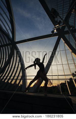 backlight image of a woman dancing ballet on a modern bridge