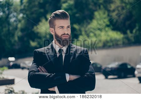 Successful Authority Young Guy In A Black Suit. So Fashionable And Stylish, Severe. Outdoors On Sunn
