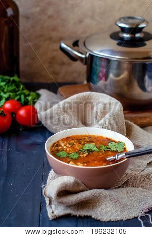 Georgian soup kharcho with cilantro and vegetables. The national Georgian dish is served with fresh lavash. Soup kharcho with vegetables and cilantro on a wooden table.