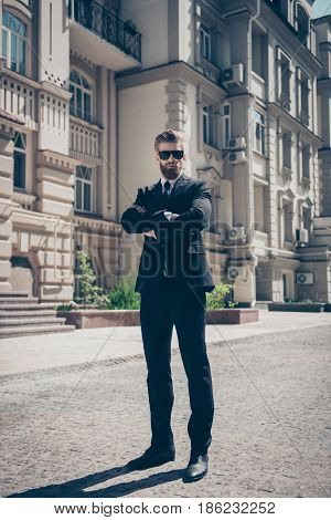 Full Size Portrait Of A Harsh Agent Outdoors. He Looks Stunning And Severe, Wearing Suit And Sunglas