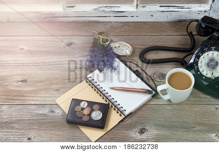 Top view of antique desktop objects coffee wallet money and nature decorations with hazy light coming in from window.