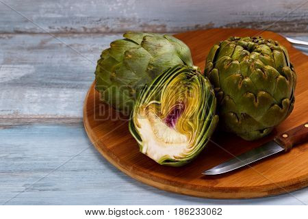 Ripe organic artichokes on cutting board and rustic wooden background