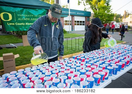 EUGENE, OR - MAY 7, 2017: Volunteers pour sports drink into cups at an aid station before the start of the 2017 Eugene Marathon race held on the University of Oregon campus.