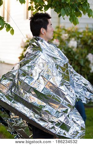 EUGENE, OR - MAY 7, 2017: Runner wraps himself in a foil blanket to stay warm prior to the start of the 2017 Eugene Marathon race held on the University of Oregon campus.