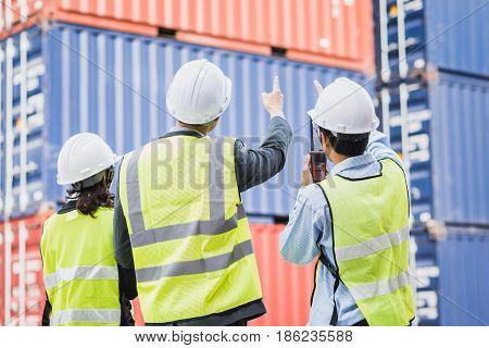 Back view of businessman with staff in logistic export import industry checking shipping cargo container freight.