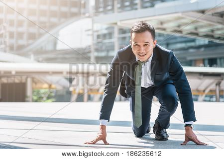 Happy confident Asian businessman ready to start his career or business with city in background. Business start concept.